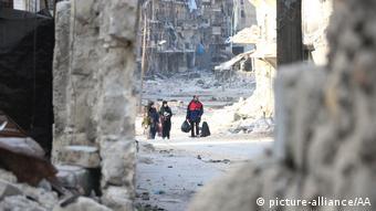 Residents escape Assad regime bombardment in the Al Moyaser neighborhood of Aleppo on November 29