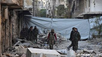 Syrian government soldiers walk amid rubble of damaged buildings after taking control of al-Sakhour neighborhood in Aleppo