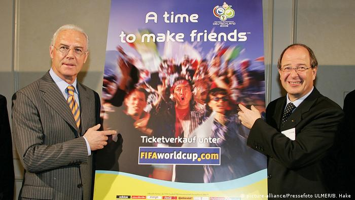 Beckenbauer and Linsi hold a 2006 World Cup poster (picture-alliance/Pressefoto ULMER/B. Hake )