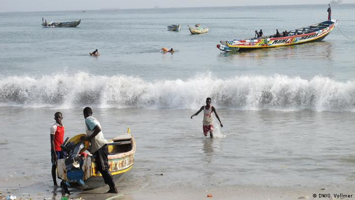 People pulling small boats to the shore and wading through the sea