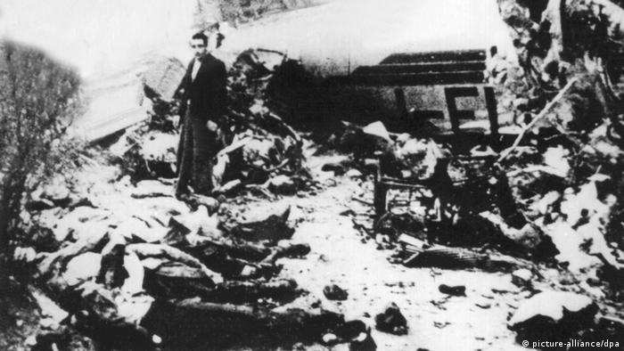 Homem olha para a câmera em meio aos destroços do avião