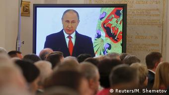 Vladimir Putin is seen on a screen during his annual state of the nation address at the Kremlin in Moscow, Russia