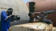 04.03.2015 TO GO WITH AFP STORY BY AMY FALLON Ramon Film Productions and founder of Wakaliwoods Isaac Nabwana, directs and films a scene in one of their up coming movies in Kampala, on March 4, 2015. It is being filmed in a scrap yard in Wakaliga, a slum in Uganda's capital Kampala now baptised Wakaliwood. It is going to be as big as Nollywood, Bollywood or even Hollywood - there's no reason why not, writer, director, editor and producer Isaac Nabwana boasted of Uganda's informal film industry -- boldly insisting studios in Nigeria, India and the United States will get a run for their money. AFP PHOTO/ ISAAC KASAMANI (Photo credit should read ISAAC KASAMANI/AFP/Getty Images)