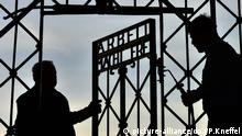 ARCHIV- Metallarbeiter montieren am 29.04.2015 in der KZ-Gedenkstätte Dachau in Dachau bei München (Bayern) das rekonstruierte Metalltor mit der Aufschrift Arbeit mach Frei Das Original war Ende 2014 von Unbekannten gestohlen wurde. Foto: Peter Kneffel/dpa (zu dpa Gestohlenes KZ-Tor aus Dachau vermutlich in Norwegen aufgetaucht vom 02.12.2016) +++(c) dpa - Bildfunk+++