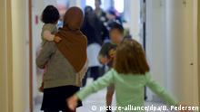 Eine Frau trägt am 29.03.2016 in Berlin in einer Notunterkunft ihr Kind auf dem Arm. Foto: Britta Pedersen/dpa | Verwendung weltweit
