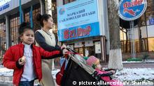TASHKENT, UZBEKISTAN - NOVEMBER 28, 2016: A woman with kids walks past the campaign headquarters of Uzbekistani presidential candidate Shavkat Mirziyoyev ahead of the 2016 Uzbekistani presidential election scheduled for December 4, 2016. Valery Sharifulin/TASS |