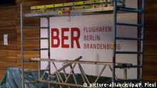 ARCHIV - Ein Baugerüst steht am 12.10.2016 in einem Gebäude vor einem Schild des Hauptstadtflughafens Berlin Brandenburg Willy Brandt (BER) in Schönefeld (Brandenburg). Das geplante Regierungsterminal am neuen Hauptstadtflughafen beschäftigt am 02.12. abermals den Aufsichtsrat der Flughafengesellschaft. Themen im Kontrollgremium sind auch der Stand der Arbeiten im neuen Flughafen und der Wirtschaftsplan der Flughafengesellschaft für 2017. (zu dpa BER-Akteure kämpfen auch beim Regierungsterminal gegen die Uhrvom 01.12.2016) +++(c) dpa - Bildfunk+++   Verwendung weltweit