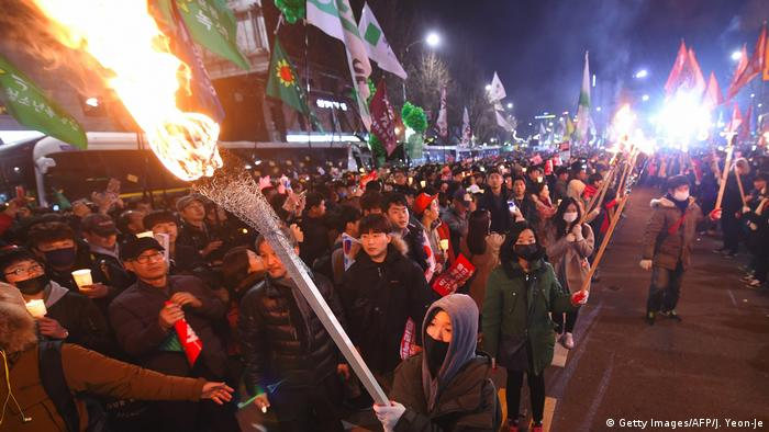 Protesters carry torches as they march toward the presidential Blue House during a rally against South Korea's President Park Geun-Hye in central Seoul