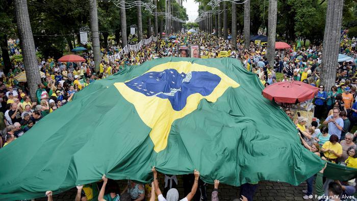 Manifestantes cobrem passeata com bandeia brasileira em protesto contra corrupção, em Belo Horizonte em dezembro de 2016