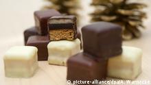 ILLUSTRATION - Dominosteine mit Kouvertuere aus Vollmilch, Zartbitter und weißer Schokolade liegen am 23.10.2014 in Berlin auf einem Tisch. | Verwendung weltweit