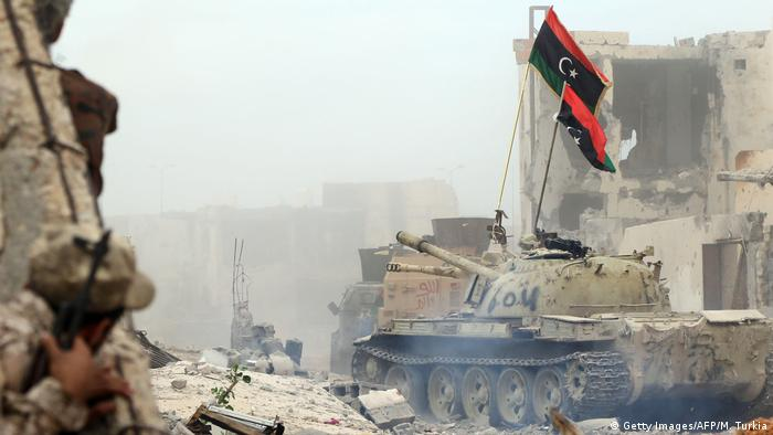 A member of forces loyal to Libya's Government of National Accord (GNA) takes cover behind a wall
