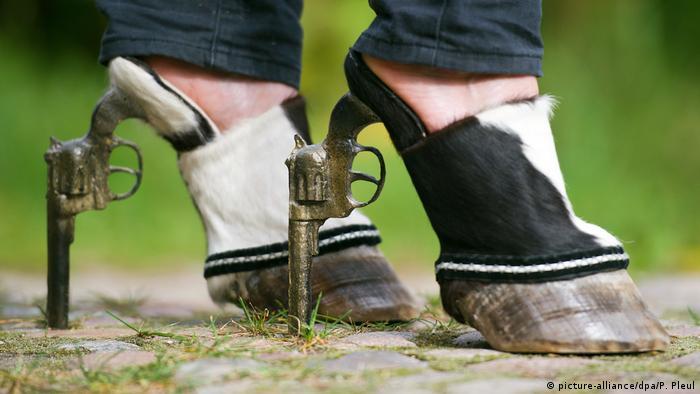 Sapato em forma de casco de boi e com revólver como salto