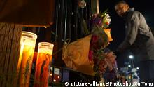 Ein Mann legt zum Gedenken an die Todesopfer Blumen nieder