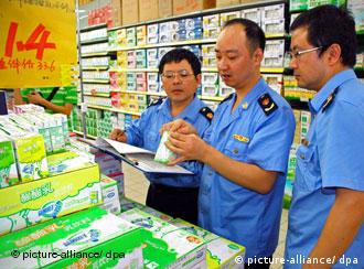 Chinese officials looking at milk cartons in a store