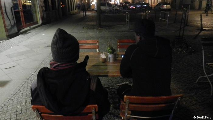 Two Gambian refugees sitting at a table at a cafe in Berlin