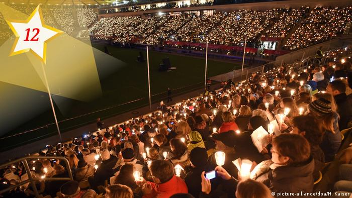 People singing Christmas songs in a stadium (picture-alliance/dpa/H. Kaiser)