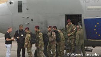 Members of the EU observer mission dressed in camo getting off of a large military plane with the EU flag on the side of it.