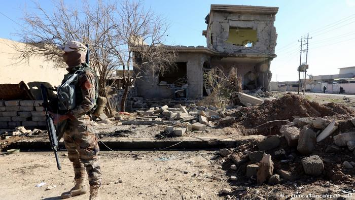 An Iraqi soldier stands next to a house destroyed during clashes between Iraqi forces and Islamic state fighters (IS) at the al-Intisar district, southeast of Mosul (picture-alliance/dpa/A. Jalil)