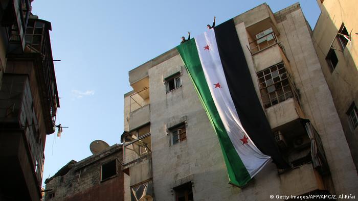Флаг Сирии на здании в Алеппо