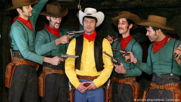 Schauspieler Til Schweiger mit gelben Hemd, roten Halstuch und weißen Hut wird von vier Schauspielern mit Pistolen umringt (Foto: picture-alliance/dpa/J. Carstensen).