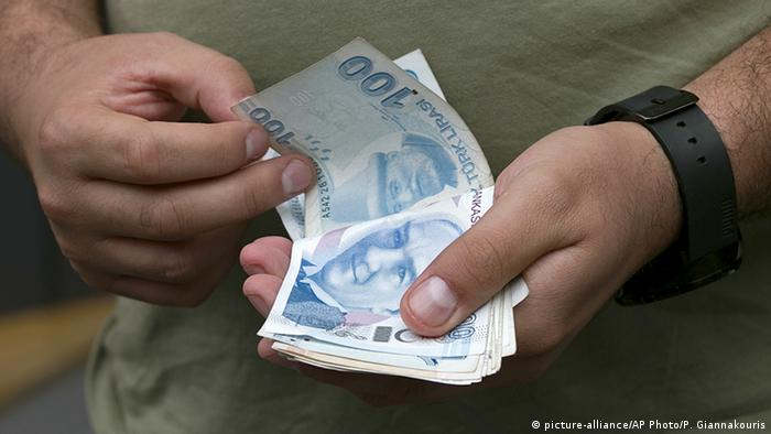 A man counts his Turkish liras as he leaves from a currency shop in central Istanbul