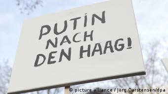 Путина - в Гаагу, написано на плакате протестующего у посольства РФ в Берлине, 7 декабря 2016 года