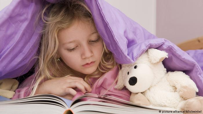 Girl lies under a duvet with a book and teddy