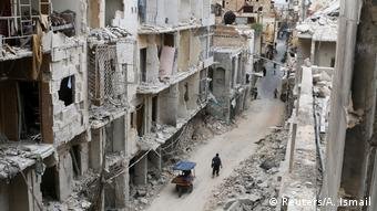Residents walk near damaged buildings in the Old City of Aleppo,