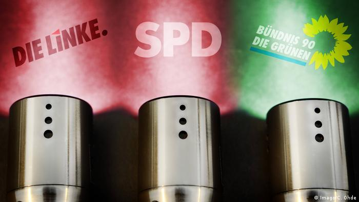 German Left Party, SPD and Green Party logos in torch spotlights