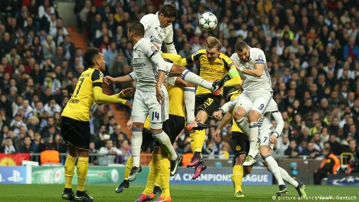 Футболисты в борьбе за мяч играют головой - Боруссия (Дортмунд) против Реала (Мадрид)