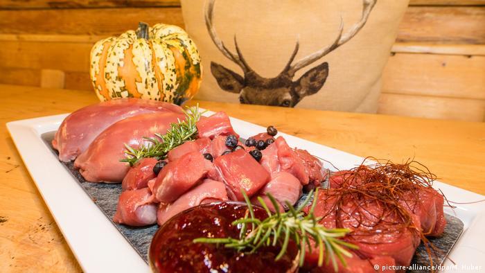 Rohes Wildfleisch liegt auf einem Teller neben einem Kürbis (picture-alliance/dpa/M. Huber)