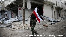 A Syrian soldier holds the Syrian nationals flag in eastern Aleppo