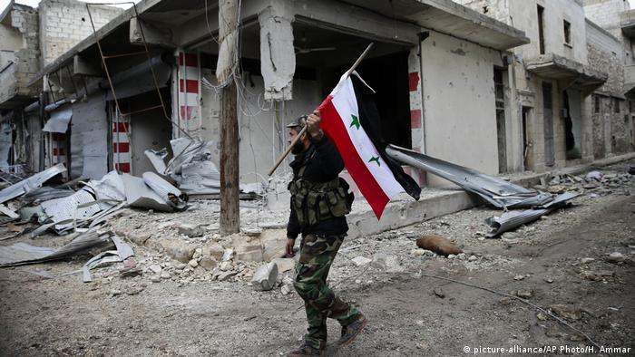 Syrien syrischer Soldat mit Flagge (picture-alliance/AP Photo/H. Ammar)