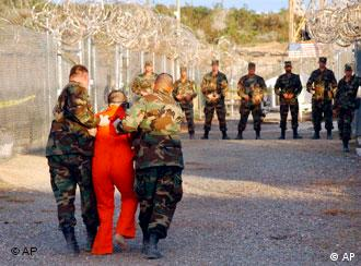 U.S. Army Military Police escort a detainee to his cell in Camp X-Ray at Naval Base Guantanamo Bay, Cuba