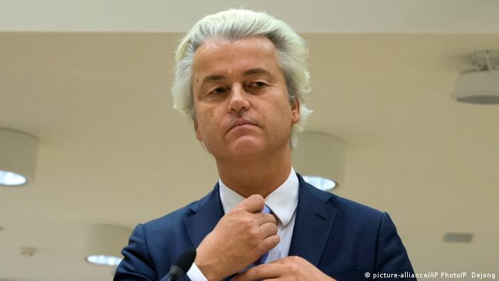 Geert Wilders adjusting his tie during a hate speech trial (picture-alliance/AP Photo/P. Dejong)
