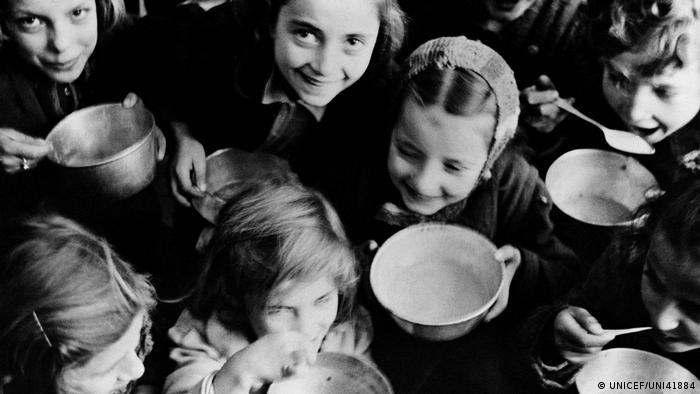 small children holding out bowls (UNICEF/UNI41884)