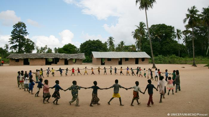 many children holding hands in a circle (UNICEF/UNI46342/Pirozzi)