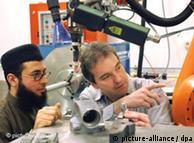Два ученых, один из которых иностранец, наблюдают за работой прибора