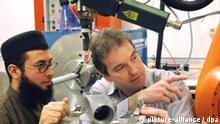 Jena (Thüringen): In einem Speziallabor für Lasertechnik der Fachhochschule Jena sind am 23.01.2003 der Wissenschaftler Prof. Jens Bliedtner und der syrische Student Housam Zakkour (l) in ein Fachgespräch vertieft. Bereits seit fünf Jahren lebt Housam Zakkour in Deutschland. Nach mehreren Semestern für Pharmazie an der Universität Erlangen-Nürnberg hat sich der junge Syrer jetzt für ein Studium der Laser- und Optotechnologien an der Jenaer Bildungseinrichtung entschieden. Von den 4.230 eingeschriebenen Studentinnen und Studenten der Fachhochschule kommen 62 aus dem Ausland. In einem besonderen Programm werden künftig jährlich etwa 30 Bewerber aus China für ein Studium an der Jenaer Fachhochschule vorbereitet. (GER41-230103)