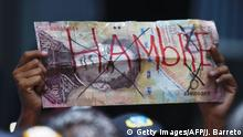 25.5.2016**** An opponent to the government of Venezuelan President Nicolas Maduro holds a sign representing a Venezuelan currency bill reading 'Hunger' during a protest outside the Supreme Tribunal of Justice (TSJ) in Caracas on May 25, 2016. Protesters seeking to drive Maduro from office launched fresh street rallies on Wednesday, a test of their strength in a tense political crisis. / AFP / JUAN BARRETO (Photo credit should read JUAN BARRETO/AFP/Getty Images)