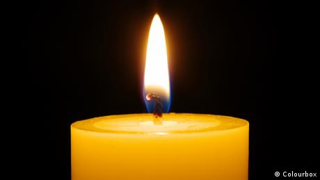A close-up image of a flame burning a white candle.
