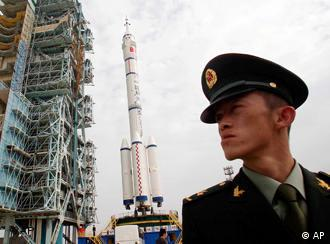 A Chinese soldier is seen guarding near the Shenzhou-7 manned spaceship, the Long-March II-F rocket, and the launch pad at the Jiuquan launch center in Jiuquan, China's northwest Gansu province, Saturday, Sept. 20, 2008. A Chinese astronaut will conduct the country's first spacewalk on Friday afternoon local time, state media reported. (AP Photo/Color China Photo) ** CHINA OUT **