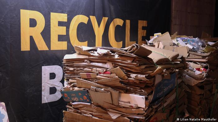 Trash piled in front of a sign saying Recycle Beirut