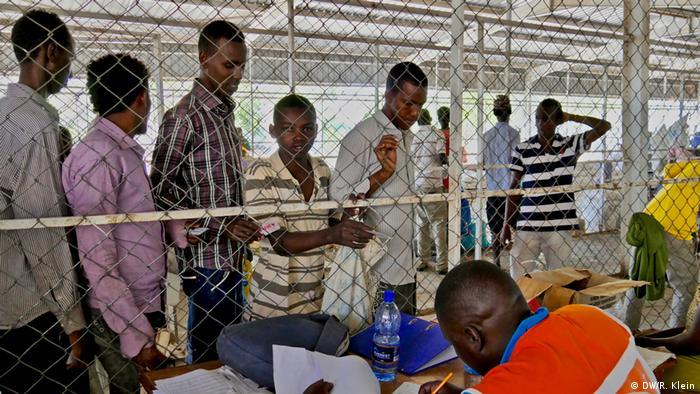 Hacer colas para recibir las respectivas raciones demora hasta cinco horas. Los trabajadores son aislados por una malla de alambre para protegerlos de la violencia que puede surgir ante la desesperación de la escasez y el hambre.