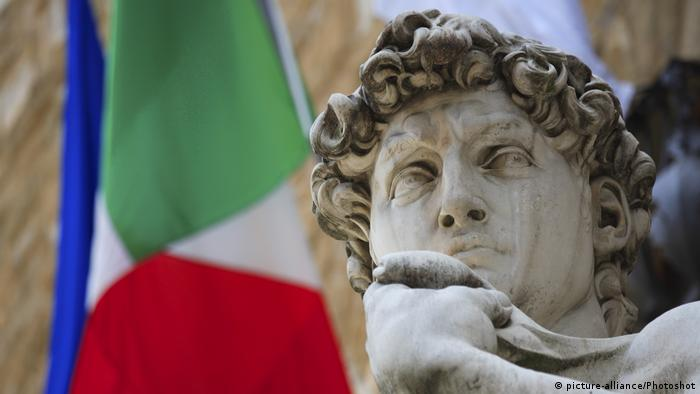 Michelangelo's statue David in front of an Italian flag