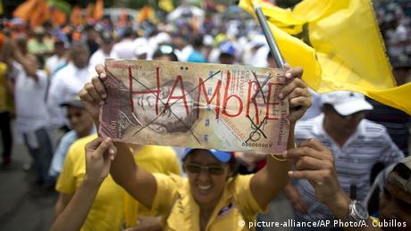 Venezuelan protester holds a banknote
