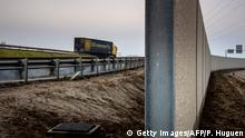13.12.2016 *** A photo taken on December 13, 2016 in Calais, shows a four-metre-high (13-foot) wall, running along a kilometre-long stretch of the main road leading to Calais port, aimed at stopping migrants from the former Calais jungle camp who attempt to reach its shores. The wall was built to boost a network of wire fences that had failed to prevent near nightly attempts by migrants to waylay trucks en route to Europe's second-busiest port. Calais has for years been a staging post for attempts by migrants to sneak into Britain by stowing away on trucks or trains crossing the Channel. / AFP / PHILIPPE HUGUEN (Photo credit should read PHILIPPE HUGUEN/AFP/Getty Images)