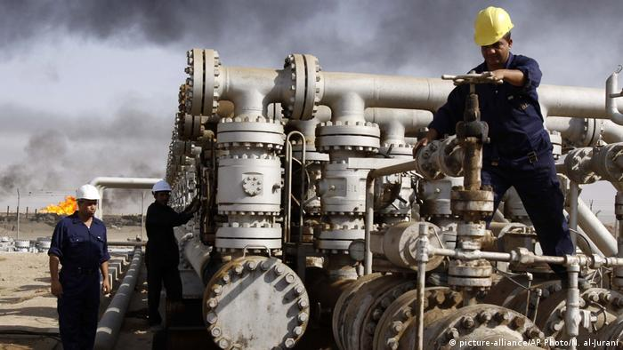 Oil workers at the Rumaila oil refinery, near the city of Basra, Iraq