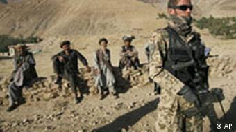 Afghan men look on as ISAF soldiers with the German Federal Armed Forces (Bundeswehr) patrol the mountain villages in the outskirts of Feyzabad, northern Afghanistan