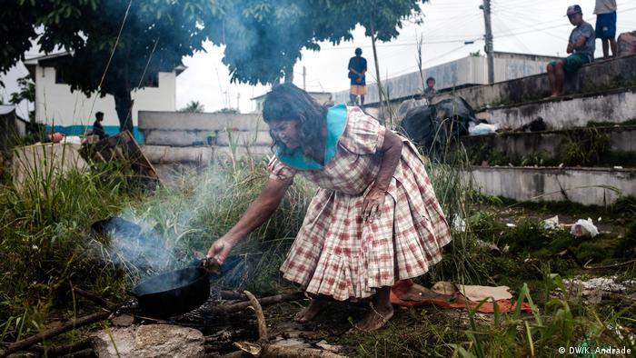 Índia venezuelana da etnia Warao cozinha em terreno baldio, no centro de Pacaraima.